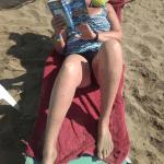 """Silvia im Urlaub auf Kreta, am Strand liegend, mit Buch """"111 Gründe Finnland zu lieben"""" in der Hand"""
